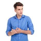 Besorgter junger Mann, der seine Hände zusammenhält Stockfotos