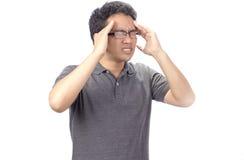 Besorgter junger Mann, der unter Kopfschmerzen leidet Stockfotos