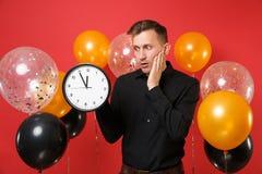 Besorgter junger Mann im klassischen Hemd, das Hand auf der Backe, runde Uhr auf roten Hintergrundluftballonen halten hält Zeit i stockfoto