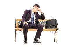 Besorgter junger Wirtschaftler, der auf einer Holzbank sitzt Lizenzfreies Stockbild