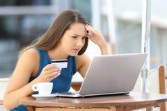 Besorgter Käufer, der mit Kreditkarte zahlt Stockfoto