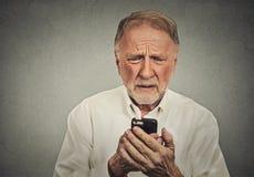 Besorgter älterer Mann, der sein intelligentes Telefon betrachtet Stockfoto