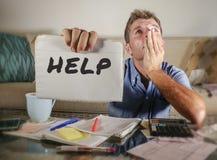 Besorgter Mann im Druck zu Hause, der Monatssteuerausgaben mit den Taschenrechnerbuchhaltungszahlungen traurig und das deprimiert Lizenzfreies Stockfoto