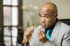 Besorgter Mann mit einer Opiod-Verordnungs-Pille Stockbild