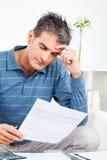 Besorgter Mann mit Rechnungen Stockbilder