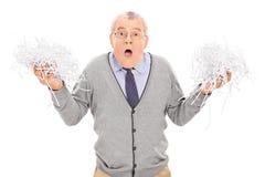 Besorgter Senior, der einen Stapel des zerrissenen Papiers hält Stockbilder