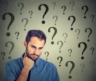 Besorgter trauriger Mann hat viele Fragen, die unten schauen Stockbild