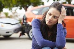 Besorgter weiblicher Fahrer Sitting By Car nach Verkehrsunfall Lizenzfreie Stockbilder