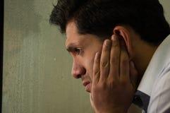 Besorgter widergespiegelter junger Mann depresed, grauer Hintergrund Lizenzfreies Stockbild