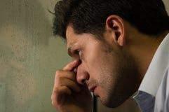 Besorgter widergespiegelter junger Mann depresed, grauer Hintergrund Stockfotos