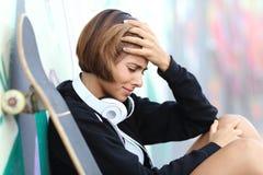 Besorgtes Jugendlichmädchen, das auf einer Wand mit Graffitis sich lehnt Stockbild