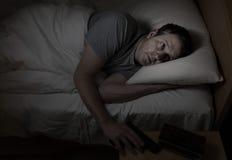 Besorgtes Mannzupacken schießt vom Nachtstand während im Bett Lizenzfreies Stockbild