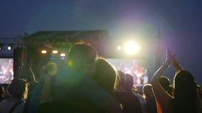 Besos cariñosos de los pares en el festival de la roca en el aire abierto, muchedumbre de gente iluminada por la luz colorida dur almacen de metraje de vídeo