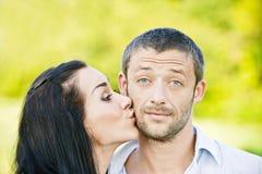 Besos de la mujer adentro en hombre de la mejilla Foto de archivo
