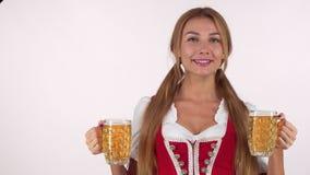 Besos que soplan de la muchacha preciosa de Oktoberfest a la cámara, sosteniendo dos tazas de cerveza grandes almacen de video