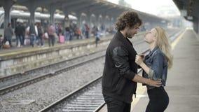 Besos que soplan de los pares adolescentes apasionados y abrazo de esperar en la estación de tren ferroviaria antes del viaje almacen de metraje de vídeo