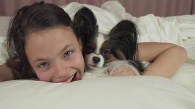 Besos y juegos adolescentes felices de la muchacha con el perro Papillon en vídeo de la cantidad de la acción de la cama almacen de video