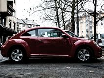 Besouro brilhante da VW do vermelho no parque de estacionamento Fotografia de Stock