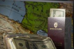 Besparing för den europeiska drömmen: dollar och pass i förgrunden royaltyfri bild