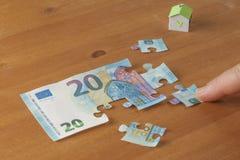 Besparing om een huisconcept te kopen: hand die een stuk op een 20 euro zetten Stock Afbeelding