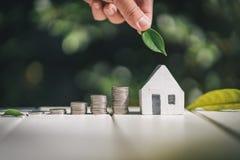 Besparing som köper ett hus- eller bilbesparingbegrepp med att växa för pengarmyntbunt coins sparande för stapel för begreppshand Royaltyfria Bilder