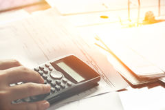 Besparingar, finanser, ekonomi och hem- begrepp - som är nära upp av man med räknemaskinen som hemma räknar danandeanmärkningar Arkivfoto