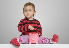 Besparingar och bankrörelsebegrepp Barnflickan sätter mynt i den piggy pengarbanken royaltyfri fotografi