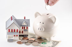 Besparingatt bygga/köp ett hem/ett hus Spargris med myntet som det är Arkivbild