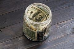Besparingbegrepp - valuta i den glass kruset Arkivfoto