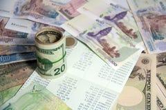 Besparingbegreppet, är det en ekonomi av eller förminskning i pengar Boka banken i mitt av pengar, inkludera rullUSA-sedlar Fotografering för Bildbyråer
