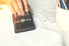 Besparingen, financiën, economie en bureauconcept Bedrijfs mensen die op calculator tellen Royalty-vrije Stock Fotografie