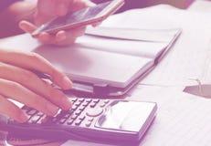 Besparingen, financiën, economie en huisconcept - sluit omhoog van de mens met calculator die makend nota's en houdend telefoon t Stock Afbeelding