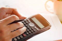 Besparingen, financiën, economie en huisconcept - sluit omhoog van mens die met calculator die nota's de maken op kantoor tellen Stock Afbeeldingen