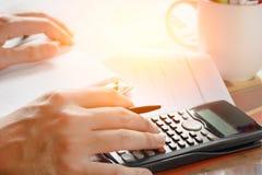 Besparingen, financiën, economie en huisconcept - sluit omhoog van mens die met calculator die nota's thuis de maken tellen Stock Fotografie