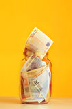 Besparingeuropengar i den glass kruset royaltyfri fotografi