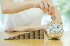 Besparings geld-jonge vrouw die een muntstuk zetten in een geld-doos Stock Foto