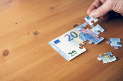 Besparingsconcept: hand die een stuk op een euro raadsel 20 zetten Stock Foto's