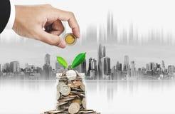 Besparingsgeld en investeringsconcept Hand die muntstuk in glaskruik zetten met installatie het groeien, stadsachtergrond stock foto