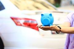 Besparingsgeld en leningen voor autoconcept, Jonge vrouw die blauwe piggy met status houden bij de achtergrond van het autoparkee royalty-vrije stock foto