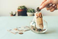 Besparingsgeld, euro muntstukken die door vingers over een kruik geld worden gehouden royalty-vrije stock fotografie