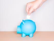 Besparingsgeld, hand die een muntstuk zetten in spaarvarken Royalty-vrije Stock Foto's