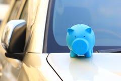 Besparingsgeld voor autoconcept, Blauwe piggy status op de auto, Autozaken stock foto