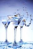 Bespat martini op blauw stock afbeeldingen