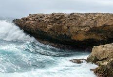 Bespattende golven bij een ruwe en rotsachtige kustlijn stock afbeelding