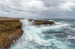 Bespattende golven bij een ruwe en rotsachtige kustlijn royalty-vrije stock afbeelding