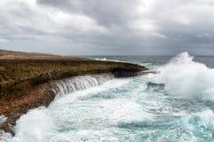 Bespattende golven bij een ruwe en rotsachtige kustlijn royalty-vrije stock afbeeldingen