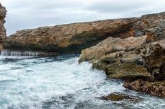 Bespattende golven bij een ruwe en rotsachtige kustlijn stock afbeeldingen