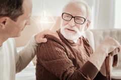 Bespectacled attentive man sitting and listening to his son. Fathers care. Bespectacled attentive aged men sitting on the bed supporting on the cane and Royalty Free Stock Photography