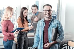 Bespectacled confident man looking straight and holding the laptop. Adore my work. Bespectacled confident handsome men standing near his colleagues looking Stock Photos