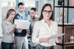 Bespectacled confident women looking straight and holding the tablet. New tablet. Bespectacled confident cute women standing in the office near her colleagues Royalty Free Stock Images